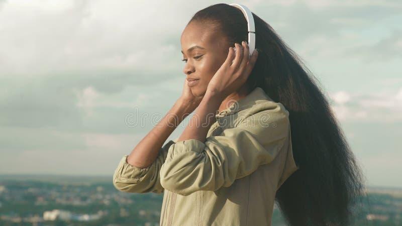 Het mooie Afrikaanse Amerikaanse meisje luistert aan muziek en geniet van Glimlachend jong zwart meisje op vage stadsachtergrond royalty-vrije stock foto