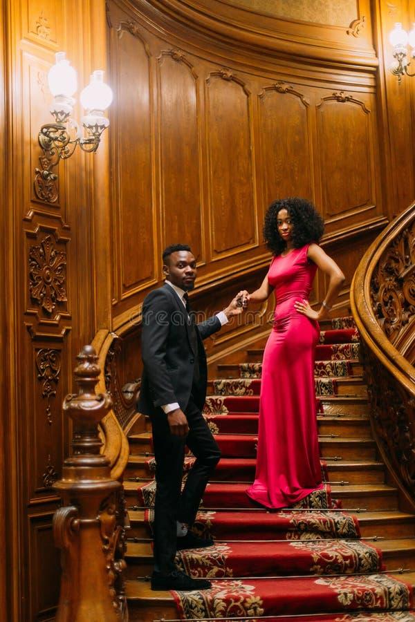 Het mooie Afrikaanse paar stellen op de uitstekende treden Luxueus theater binnenlandse achtergrond stock foto's