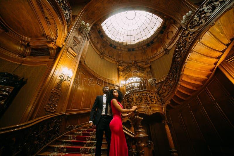 Het mooie Afrikaanse paar stellen op de uitstekende treden Luxueus theater binnenlandse achtergrond stock afbeeldingen