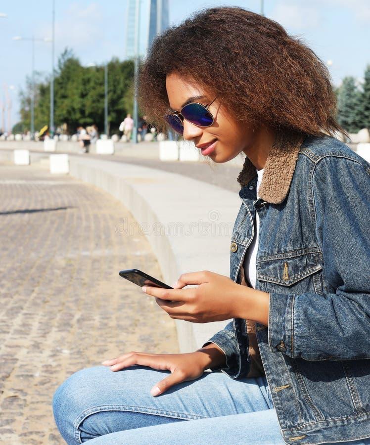 Het mooie afro Amerikaanse vrouw gebruiken mobiel in de straat Communicatie en levensstijlconcept royalty-vrije stock foto
