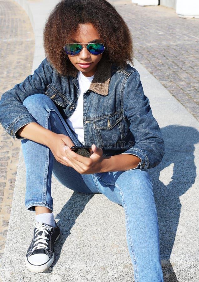 Het mooie afro Amerikaanse vrouw gebruiken mobiel in de straat Communicatie en levensstijlconcept royalty-vrije stock afbeelding