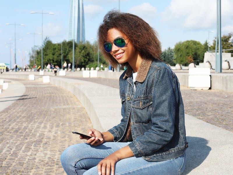 Het mooie afro Amerikaanse vrouw gebruiken mobiel in de straat Communicatie en levensstijlconcept stock afbeeldingen