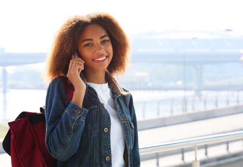 Het mooie afro Amerikaanse vrouw gebruiken mobiel in de straat Communicatie en levensstijlconcept royalty-vrije stock fotografie