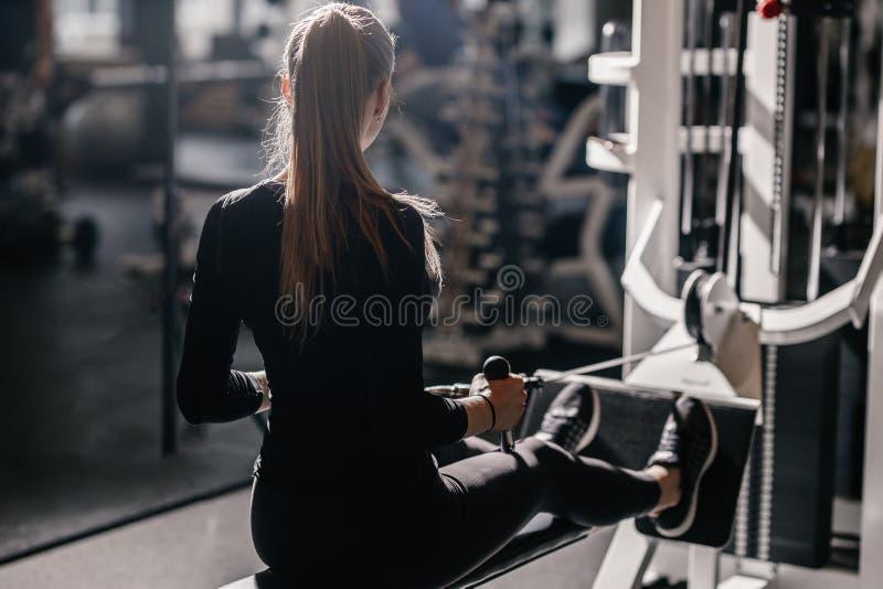 Het mooie atletische gekleed meisje gekleed in een zwarte sportkleding doet sportoefeningen met materiaal op de bank stock afbeelding