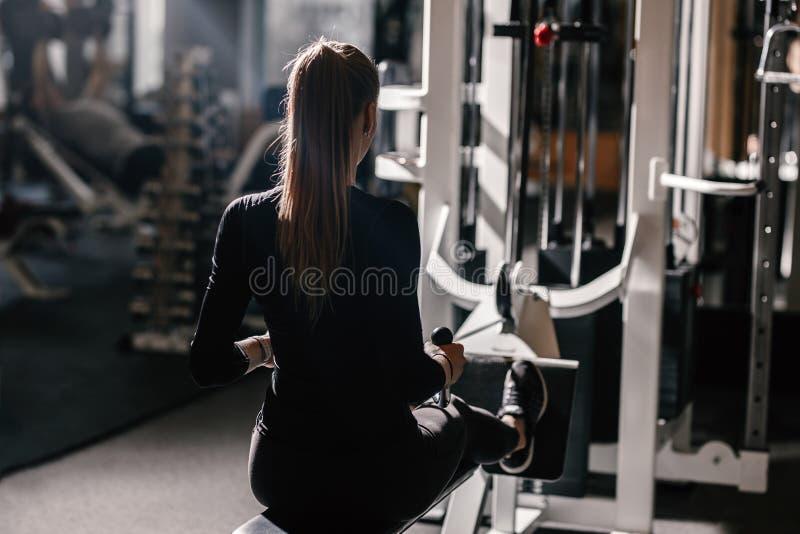 Het mooie atletische gekleed meisje gekleed in een zwarte sportkleding doet sportoefeningen met materiaal op de bank stock afbeeldingen
