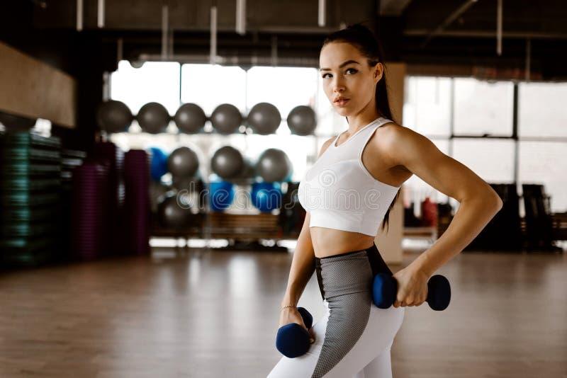 Het mooie atletische meisje gekleed in witte sportenbovenkant en legging bouwt spieren met domoren op stock fotografie