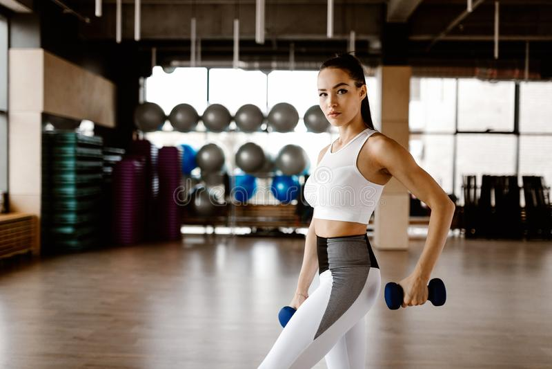 Het mooie atletische meisje gekleed in witte sportenbovenkant en legging bouwt spieren met domoren op royalty-vrije stock foto
