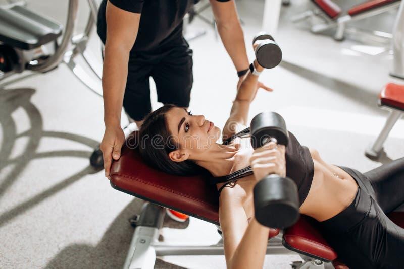 Het mooie atletische meisje gekleed in zwarte sportenbovenkant en legging bouwt spieren met domoren onder de supervisie van op stock foto's