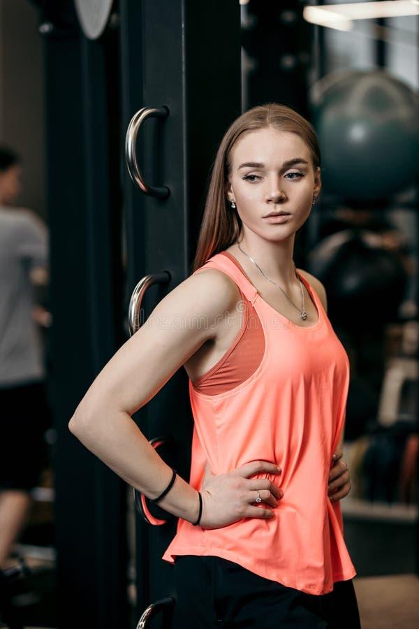 Het mooie atletische meisje kleedde zich in sportieve kleren die zich naast het sportmateriaal bevinden in de moderne gymnastiek royalty-vrije stock afbeelding