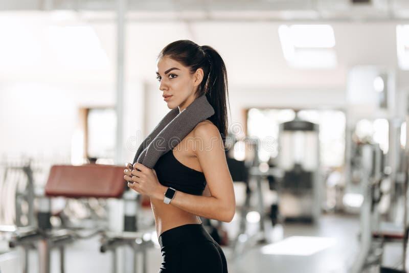 Het mooie atletische meisje kleedde zich in zwarte sportenbovenkant en leggingtribunes in de gymnastiek met de handdoek op haar s stock afbeeldingen