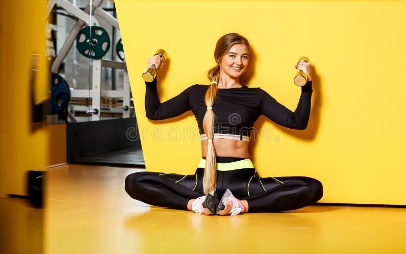 Het mooie atletische meisje met lang blond haar gekleed in een modieuze sportkleding zit op de gele vloer naast royalty-vrije stock foto