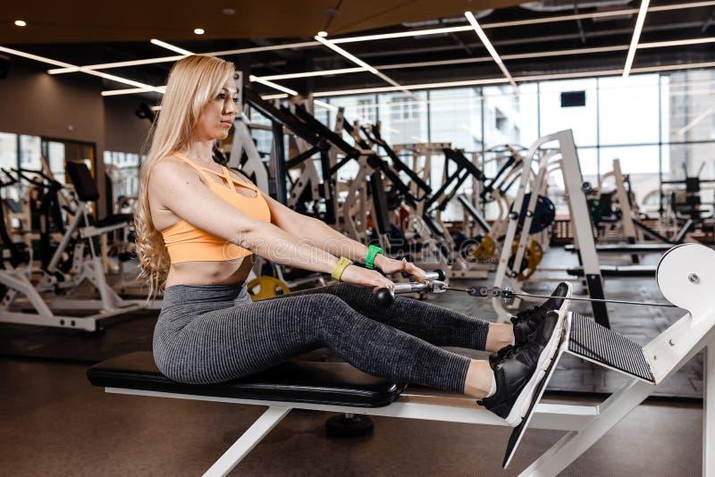 Het mooie atletische meisje met lang blond haar gekleed in een sportkleding doet sportoefeningen met materiaal op stock afbeeldingen