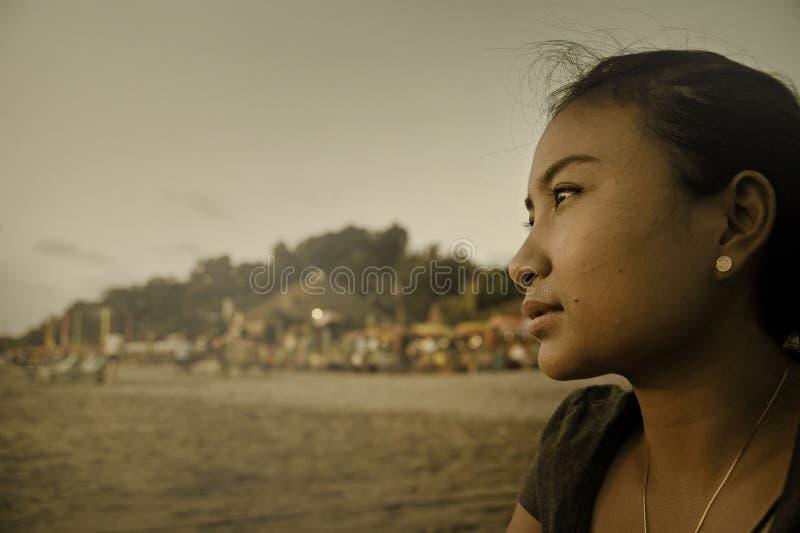 Het mooie Aziatische eenzame vrouw kijken aan oneindigheid verloor in haar gedachten droevige en nadenkende zitting op zandstrand stock fotografie
