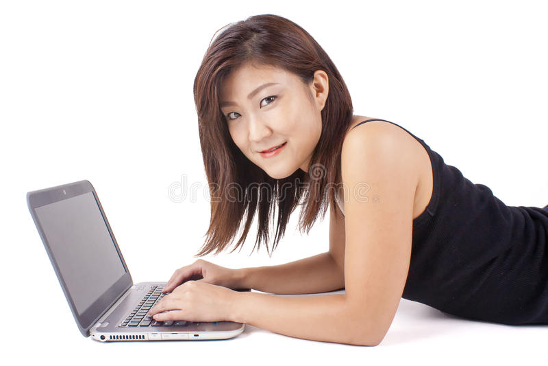 Het mooie Aziatische jonge vrouw typen op laptop stock afbeeldingen