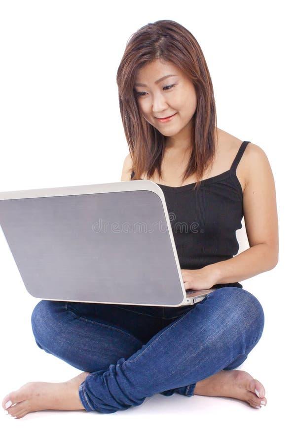 Het mooie Aziatische jonge vrouw typen op laptop stock afbeelding