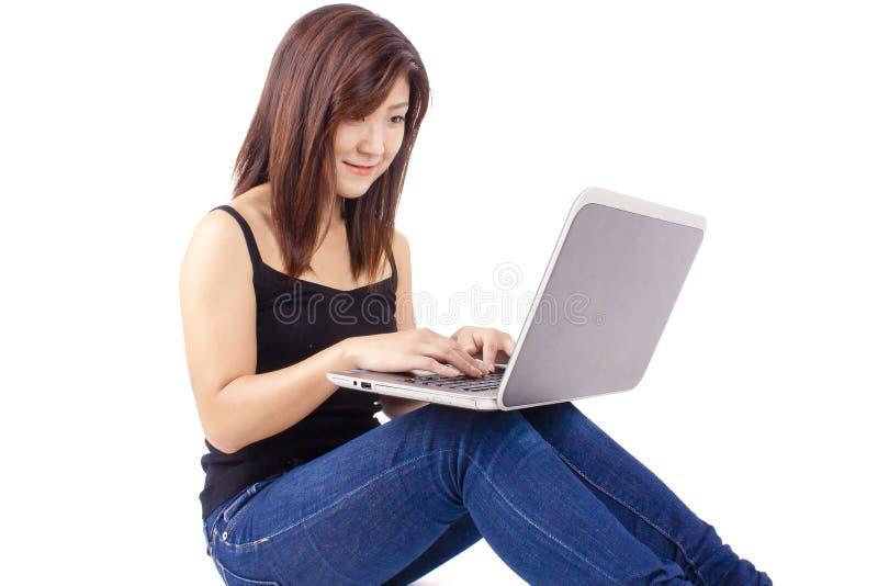 Het mooie Aziatische jonge vrouw typen op laptop royalty-vrije stock afbeeldingen