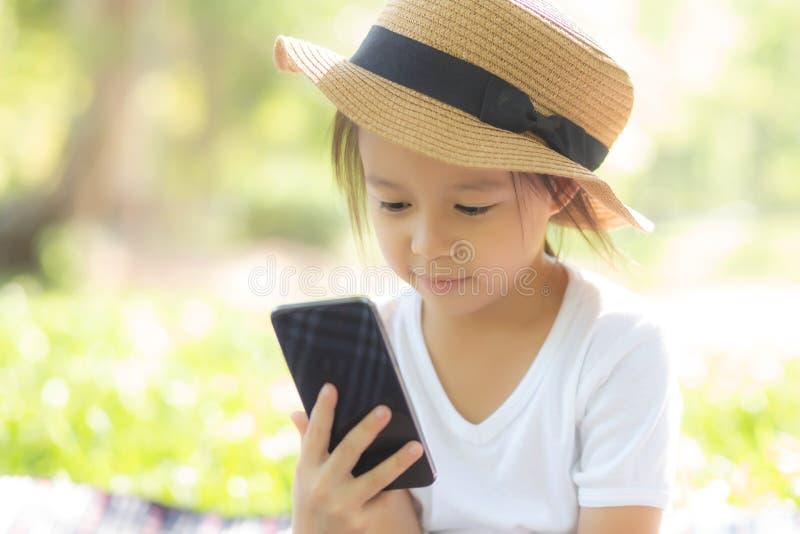 Het mooie Aziatische kind glimlachen die slimme mobiele telefoon in de tuin met behulp van, jong geitje heeft hartstochts speelsp stock foto