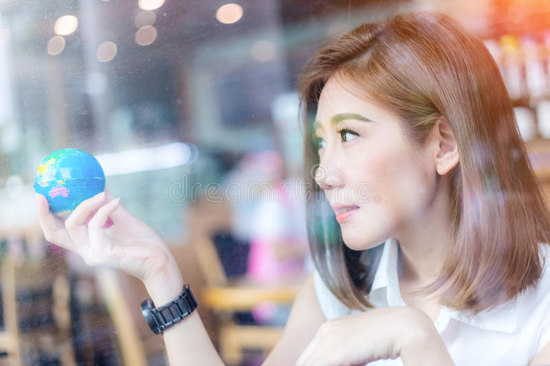 Het mooie Aziatische meisje die een bol in haar houden dient cofffeesho in stock afbeeldingen
