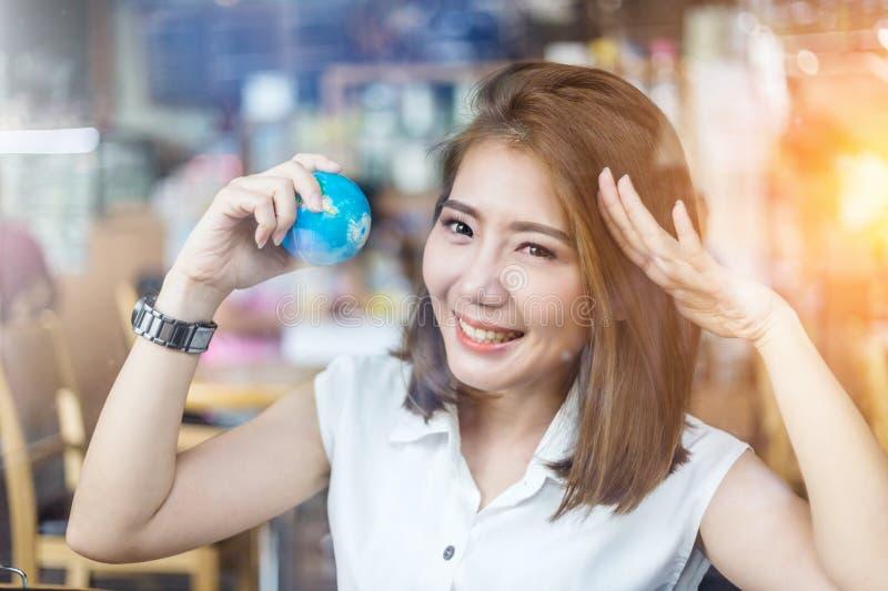 Het mooie Aziatische meisje die een bol in haar houden dient cofffeesho in stock foto