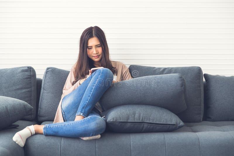 Het mooie Aziatische meisje in jeans glimlacht en zit op laag o royalty-vrije stock foto