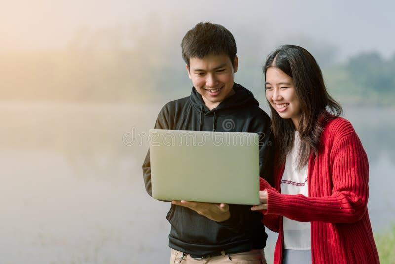 Het mooie Aziatische paar is helder in het toeristengebied Laptop de computer dient de handen van de weg amid de mist in de rug e stock afbeeldingen