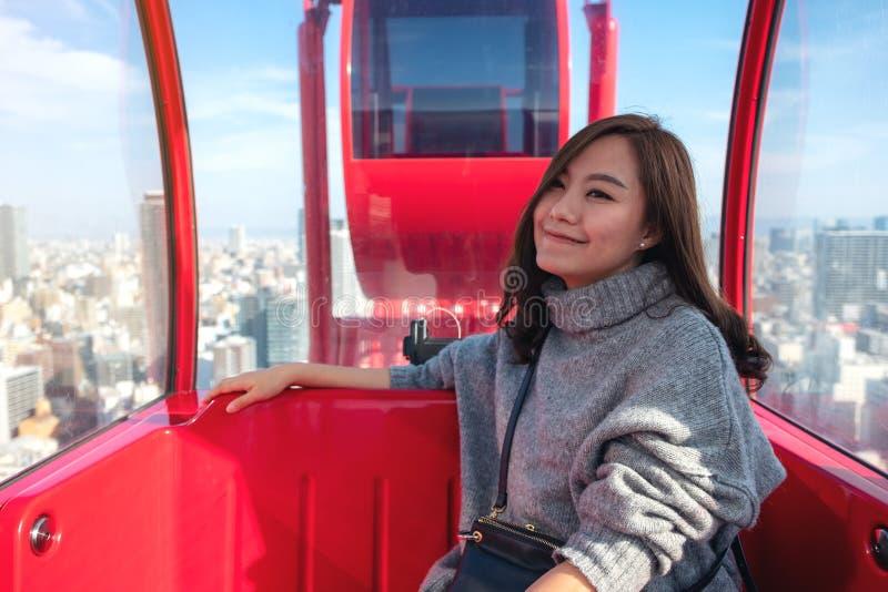 Het mooie Aziatische vrouw berijden rode ferris rijdt stock foto's