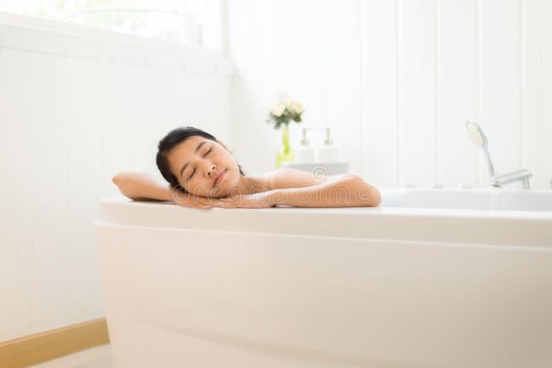 Het mooie Aziatische vrouwen dichte oog en ontspant op Jacuzzibadkuip in de ochtend, Vrouwelijk het liggen lichaam in water bij h royalty-vrije stock foto