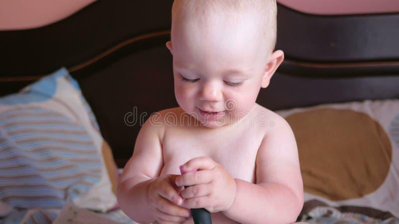 Het mooie baby spelen met kam op het bed Glimlacht en probeert om te kammen Jong geitje 1 jaar Op de kam is een spiegel stock videobeelden