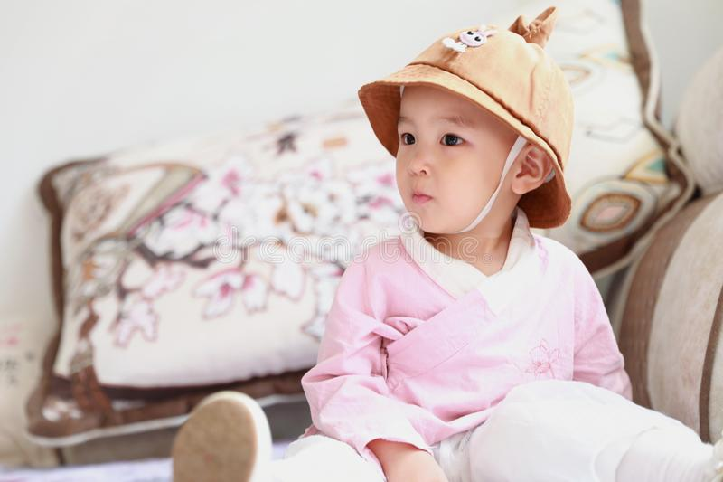Het mooie Babymeisje met een boek van de hoedenlezing gaat zitten op bank stock foto