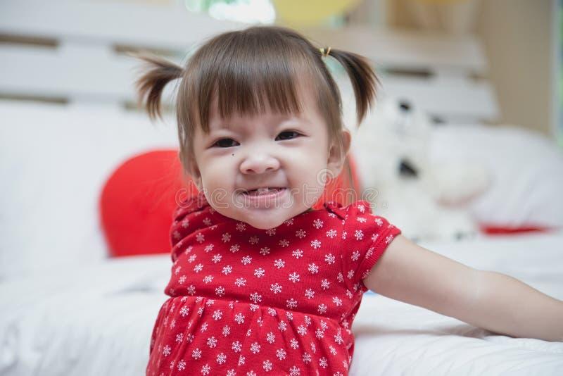 Het mooie babymeisje rood dragen glimlachend een gelukkige glimlach royalty-vrije stock fotografie