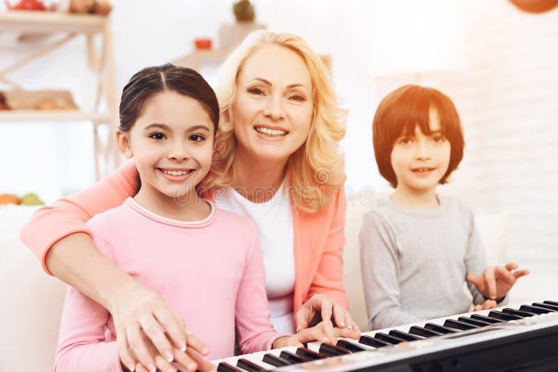 Het mooie bejaarde onderwijst kleine kleinkinderen om synthesizer te spelen stock foto