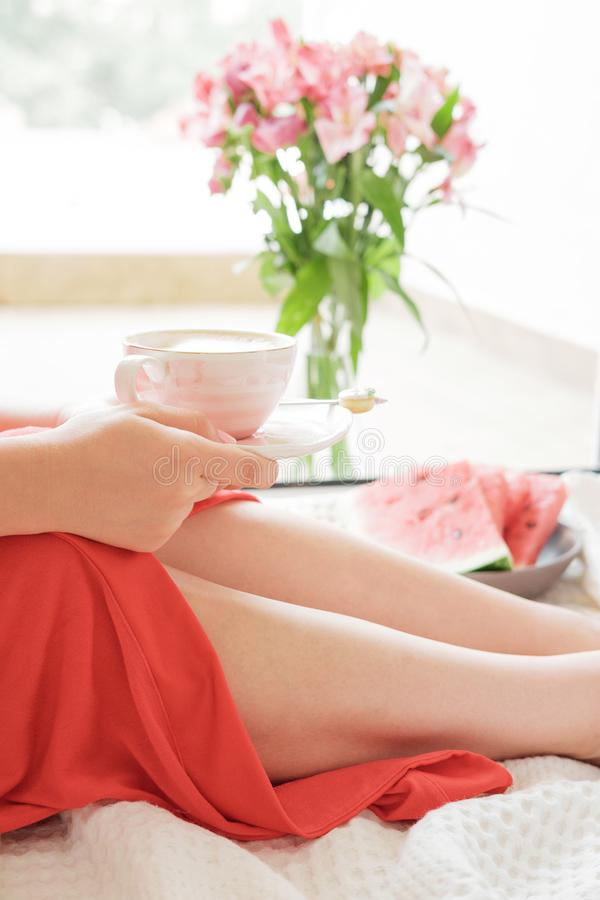 Het mooie Benenclose-up in Bed, vrouw in een rode robe drinkt coff royalty-vrije stock foto