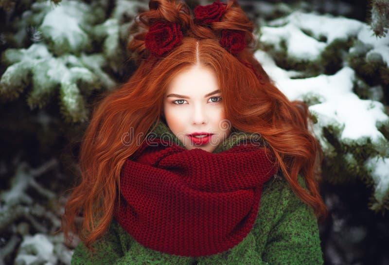 Het mooie blauwe eyed rode haired het glimlachen meisje stellen voor sneeuw behandelde sparren Fairytaleconcept stock fotografie