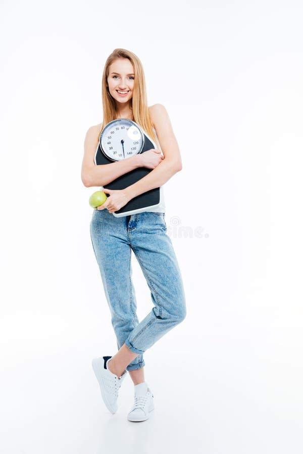 Het mooie blije vrouw stellen met schalen en groene appel stock afbeeldingen