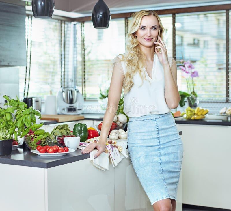 Het mooie, blonde dame realxing in de de zomerkeuken stock fotografie