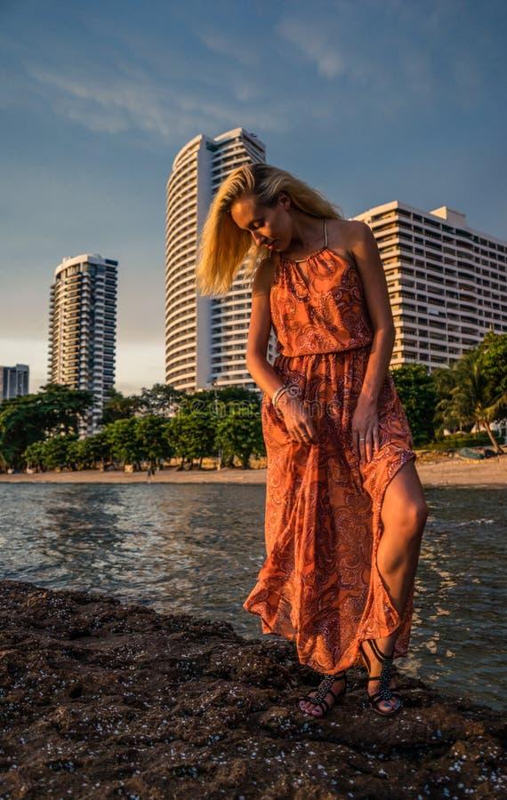 Het mooie blonde in een lichtrode kleding bevindt zich door het overzees op de achtergrond luxueuze toevlucht in het recente midd royalty-vrije stock afbeeldingen