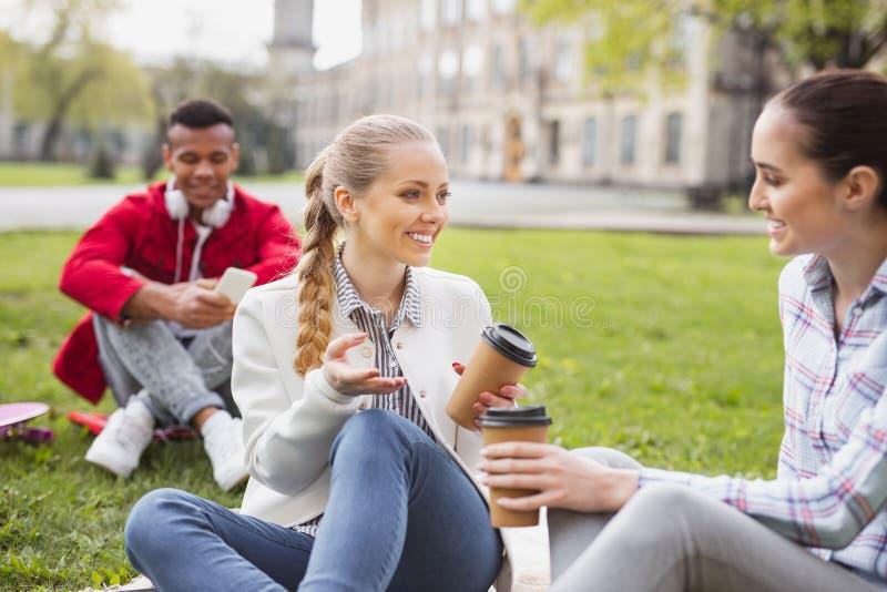 Het mooie blonde-haired student het glimlachen communiceren met groupmates royalty-vrije stock fotografie