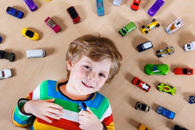 Het mooie blonde jong geitjejongen spelen met veel stuk speelgoed auto's binnen stock afbeeldingen