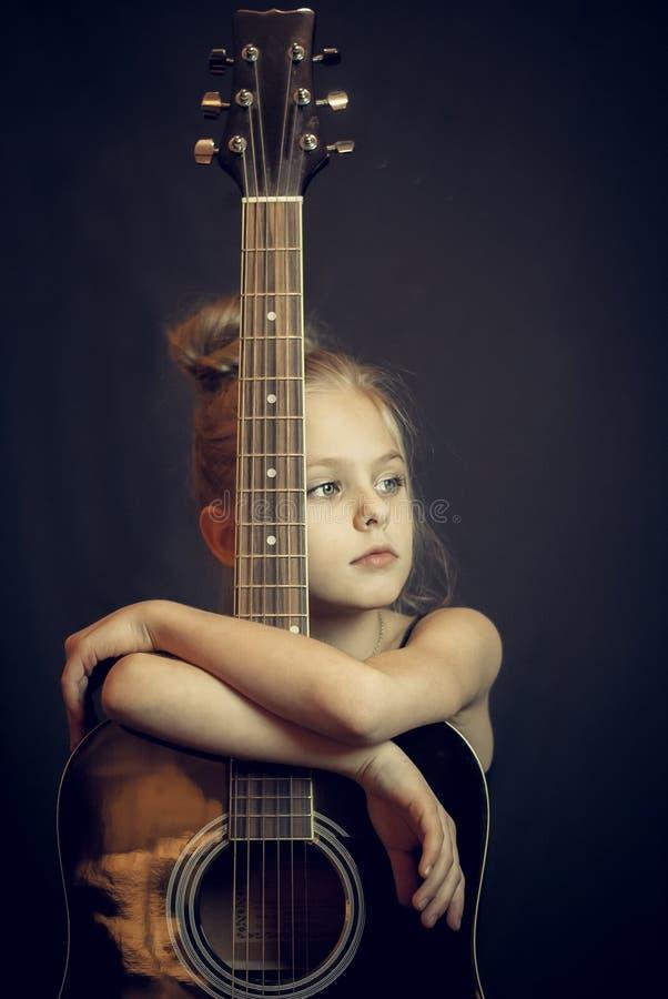 Het mooie blonde jonge meisje koestert een gitaar stock afbeeldingen