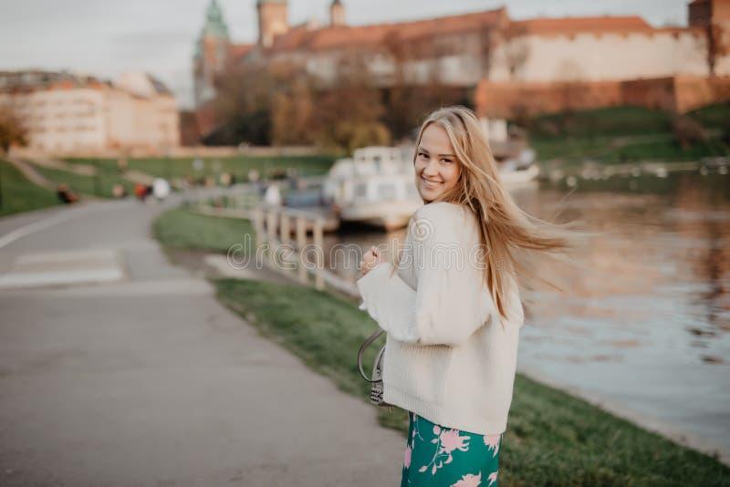 Het mooie blonde jonge vrouw lopen naast de rivier bij zonsondergang heeft pretglimlach en speelt op camera stock afbeeldingen