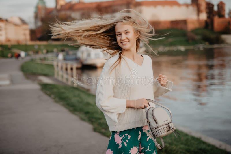 Het mooie blonde jonge vrouw lopen naast de rivier bij zonsondergang heeft pretglimlach en speelt op camera stock foto's