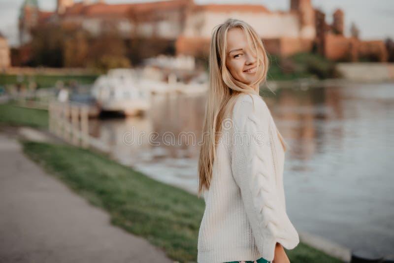 Het mooie blonde jonge vrouw lopen naast de rivier bij zonsondergang heeft pretglimlach en speelt op camera royalty-vrije stock afbeeldingen