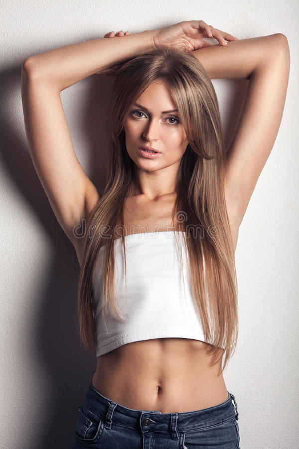 Het mooie blonde jonge vrouw stellen tegen witte muur stock fotografie