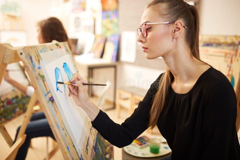 Het mooie blonde meisje in glazen gekleed in zwarte blouse zit bij de schildersezel en schildert een beeld in de kunststudio royalty-vrije stock foto's