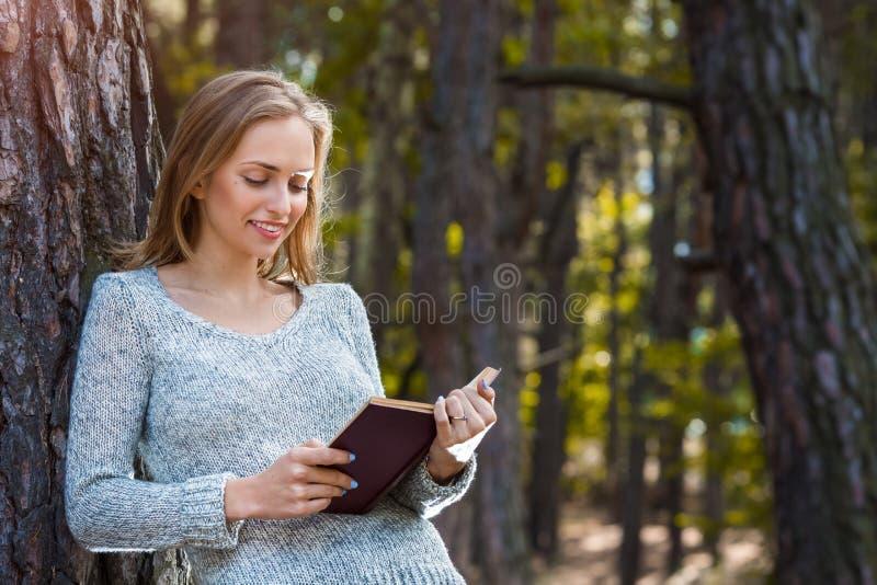 Het mooie blonde meisje rusten in de lente of de herfstbos las boek en status Zekere Kaukasische jonge vrouw binnen royalty-vrije stock foto