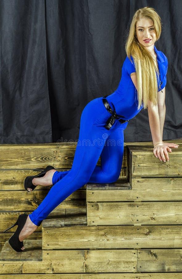 Het mooie blonde met lang haar in blauwe overall en hoge hielen die op een houten trap liggen stock afbeeldingen