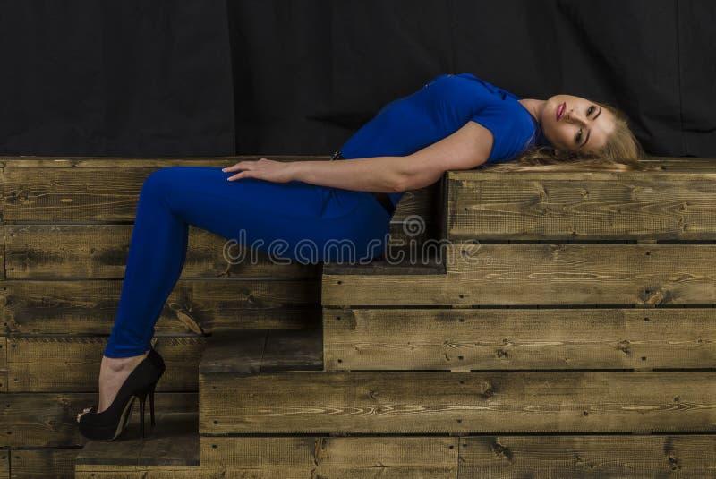 Het mooie blonde met lang haar in blauwe overall en hoge hielen die op een houten trap liggen stock fotografie