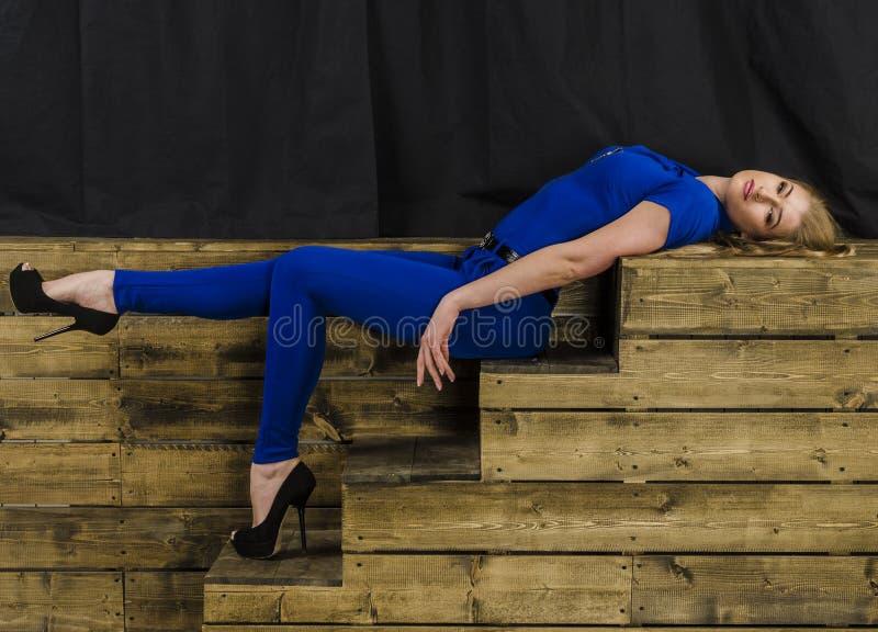Het mooie blonde met lang haar in blauwe overall en hoge hielen die op een houten trap liggen royalty-vrije stock fotografie