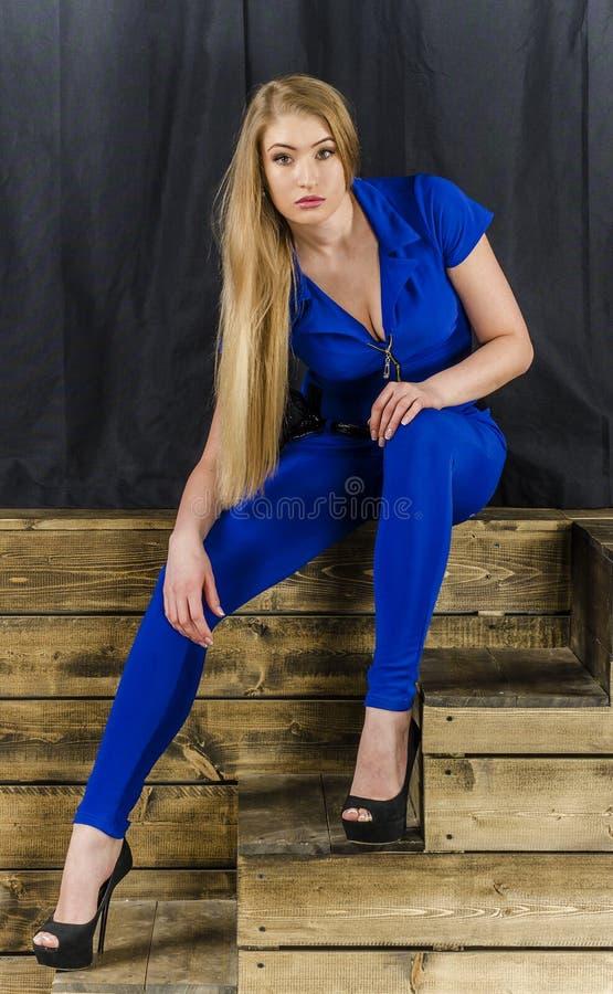 Het mooie blonde met lang haar in blauwe overall en hoge hielen die op een houten trap liggen stock foto's