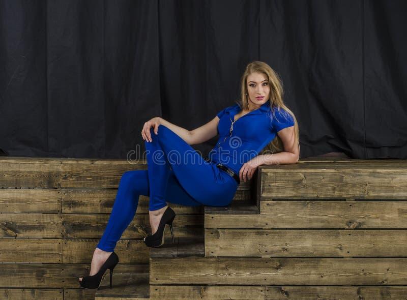 Het mooie blonde met lang haar in blauwe overall en hoge hielen die op een houten trap liggen royalty-vrije stock foto